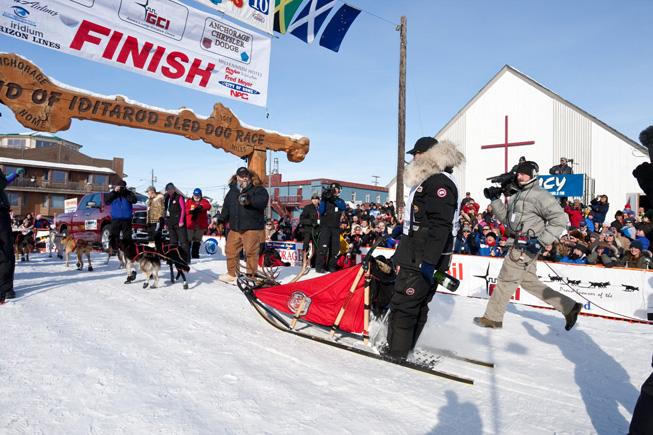 Lance Mackey runs down the crowd-linend finsih chute to win his 4th consecutive Iditarod in Nome, Alaska